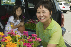 Grandmother Loading Various Flowers In Car Stock Images