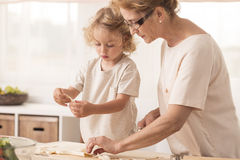 Grandmother making cookies with grandchild Royalty Free Stock Photos