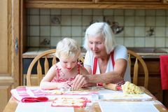 Grandmother making cookies together with granddaughter Royalty Free Stock Photography