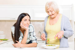 Grandmother mixing salad near her granddaughter Stock Images