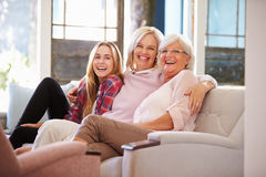 Grandmother With Mother And Adult Daughter Relaxing On Sofa stock images