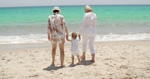 Grandmother mother and baby girl at the seaside. Three generations of the family - grandmother mother and baby girl, playing at the seaside on a sunny tropical stock video footage