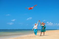 Grandmother, mother, and child launching kite on ocean beach Royalty Free Stock Photography