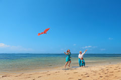 Grandmother, mother, and child launching kite on sea beach. Happy family on beach - grandmother, mother and baby girl have fun, women run along sea surf with Stock Photography