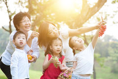 Grandmother, mother and children at outdoors. Candid portrait of beautiful multi generations Asian family at nature park. Grandmother, mother and grandchildren Stock Photography