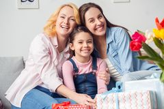 Grandmother mother and daughter together at home celebration sitting hugging smiling cheerful. Two women and girl together at home celebration sitting on sofa stock photo