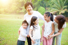 Grandmother, mother and grandchildren having fun at outdoor. Portrait of multi generations Asian family at nature park. Grandmother, mother and grandchildren royalty free stock photos