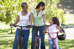Grandmother mother and granddaughter bike riding. Grandmother and granddaughter on bikes outdoors smiling Stock Images