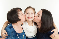 The grandmother and mother kiss the granddaughter Stock Photography