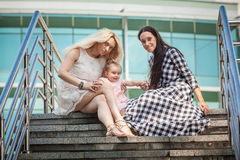 Grandmother, mother and little baby girl sitting on stairs on st Stock Photography