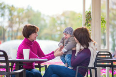 Grandmother, mother and little son in cafe. Three generations family - grandmother, mother and little son spending time together in an outdoor cafe Stock Photo