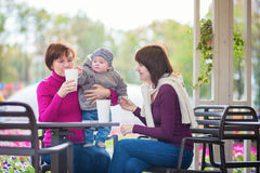 Grandmother, mother and little son in cafe. Three generations family - grandmother, mother and little son spending time together in an outdoor cafe Royalty Free Stock Image