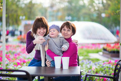 Grandmother, mother and little son in cafe. Three generations family - grandmother, mother and little son spending time together in an outdoor cafe Royalty Free Stock Photo