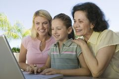 Grandmother and Mother Watching Girl Using Laptop Royalty Free Stock Photos