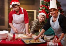 Grandmother, mum and son with christmas cake. Grandmother, mum and son making christmas cake together at home, smiling Stock Photography