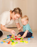 A grandmother or nanny plays with a little boy. A cute little blong haired blue eyed boy plays with his Nanny, grandmother, au pair Royalty Free Stock Photo
