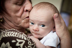 Grandmother and Newborn Grandson. Grandmother kissing cute newborn grandson Royalty Free Stock Images