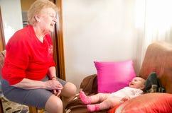 Grandmother newborn play stock photos