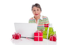 Grandmother ordered online gifts - elder woman isolated on white. Grandmother ordered online gifts. Senior lady with presents and laptop Royalty Free Stock Photo