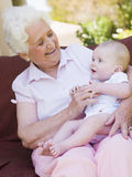 Grandmother outdoors on patio with baby Royalty Free Stock Images