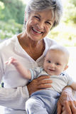 Grandmother outdoors on patio with baby Stock Photography