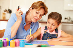 Grandmother Painting With Granddaughter At Home Stock Images