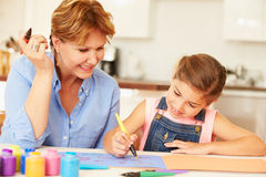 Grandmother Painting With Granddaughter At Home Stock Image