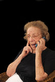 Grandmother on phone. Grandmotherly woman hearing good news on a cell phone Royalty Free Stock Images