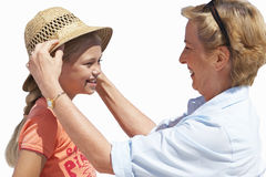 Grandmother placing sun hat on granddaughter's head, smiling, side view, cut out Royalty Free Stock Photos