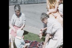 Grandmother playing with baby on blanket