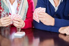 Grandmother Playing Cards With Grandson. Cropped image of grandmother playing cards with grandson at table in nursing home Royalty Free Stock Images
