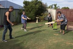 Grandmother Playing Cricket. The family is fielding in a game of Back Yard Cricket as Grandmother is batting Royalty Free Stock Images