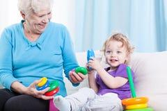 Grandmother playing with grandson. Grandmother playing cheerfully with grandson in the living room Stock Photos