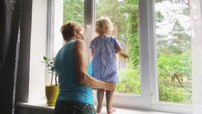 Grandmother playing and taking care of child at home. Looking through the window stock video