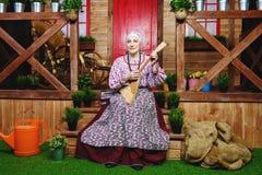 Grandmother plays balalaika Stock Photography