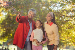 Grandmother pointing while standing with daughter and granddaughter at park Royalty Free Stock Image