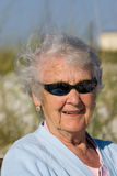 Grandmother portrait. An elderly grandmother enjoys the beach and sun Royalty Free Stock Images