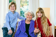Grandmother posing with her two grandchildren. Smiling elderly grey-haired grandmother posing with her two grandchildren sitting flanked by a happy little blond Stock Photography