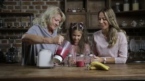Grandmother pouring berry smoothie into mason jars stock video