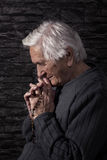 Grandmother praying. Old wrinkled beautiful woman praying with rosary. Faith, spiritualy and religion Stock Image