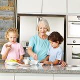 Grandmother preparing breakfast for children. Grandmother preparing a healthy breakfast for her two grandchildren in the kitchen Royalty Free Stock Photos