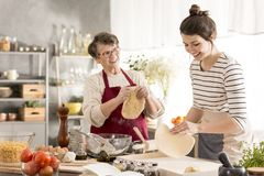 Grandmother preparing pizza with granddaughter Stock Images