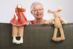 Grandmother presenting a puppet show. Happy grandmother presenting a puppet show, smiling Royalty Free Stock Photography