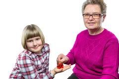 Grandmother putting euro coin in piggy bank of granddaughter Stock Images