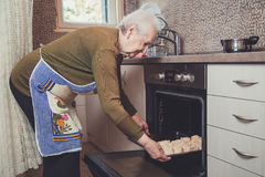 Grandmother putting pie in oven Royalty Free Stock Images
