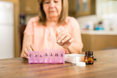 Grandmother putting tablets on a pill box Royalty Free Stock Images