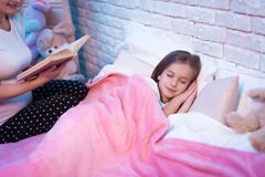 Grandmother reading book while granddaughter is lying at night at home. stock photos