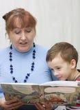 Grandmother reading a book grandson. Stock Photos