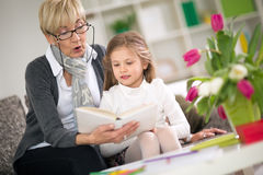 Grandmother reading book her little granddaughter Royalty Free Stock Images