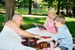 Grandmother reading a book and little boy and his grandfather pl royalty free stock photos